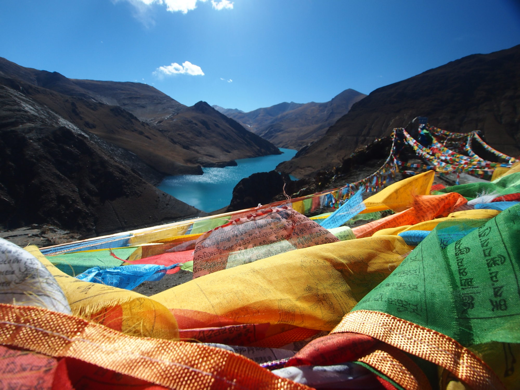 colourful prayer flags with mountains and blue sky